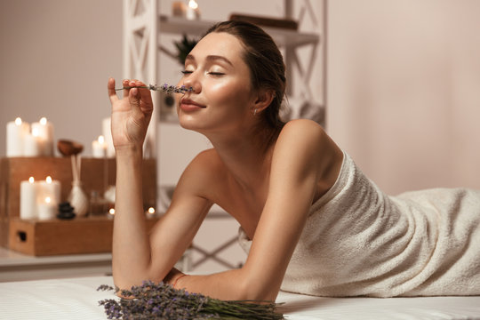 Beautiful woman lies in bathroom over candles holding lavender.