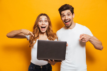 Portrait of pleased positive man and woman holding and pointing fingers at black laptop, isolated over yellow background