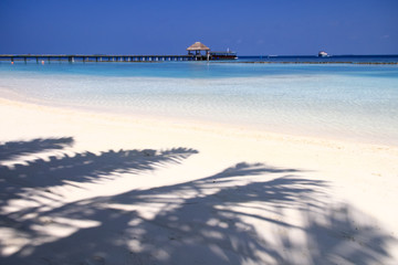 White Sand Beach, Turquoise Pacific Ocean Waters and Wood Pier .