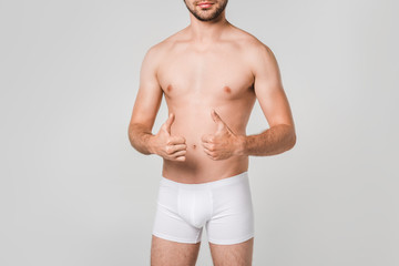 partial view of man in white underwear showing thumbs up isolated on grey