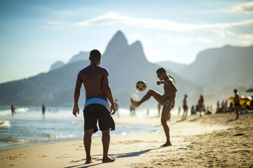 "Unrecognizable young Brazilians play a game of beach football keepy-uppy ""altinho"" on the shore of Ipanema Beach."