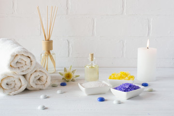 Composition of spa wellness products on white background. with towel,white lily, sea salt, bath oil, sugar body scrub and candle