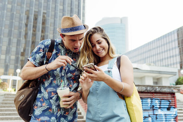 Couple browsing smartphone on street