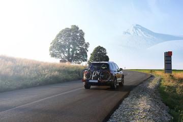 Obraz Samochód z rowerem na drodze w górach. - fototapety do salonu