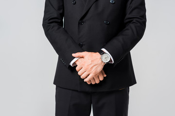 partial view of businessman in black suit isolated on grey