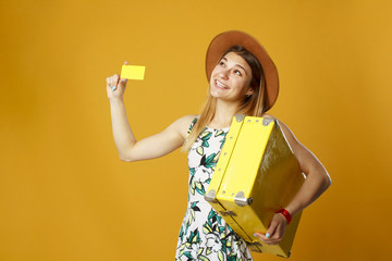 Young happy woman holding empty credit card in one hand and yellow suitcase in another over orange background