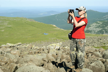 girl photographer hiker takes a picture standing on a high mountainside in the background of a mountain landscape