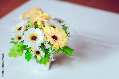 Plastic Flowers With Vases On The Table With White Cloth As The