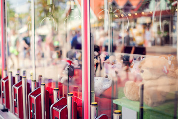 Claw machine in the amusement park of the mall which insert coin and press the control button to steel claw for pull up the doll, Skill crane or Teddy picker is game for play to fun.
