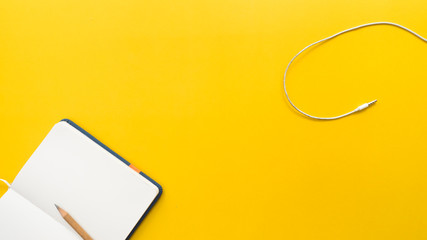 Wall Mural - earphone and  pencil with notebook on yellow background business concept