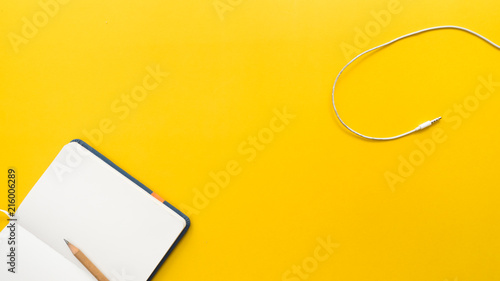 Wall mural earphone and  pencil with notebook on yellow background business concept