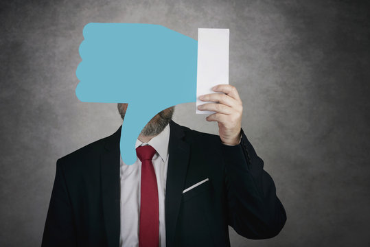 Businessman holding a dislike icon on gray background