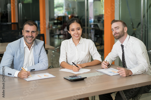 three happy business analysts working with diagrams at desk in office   business people looking at camera and sitting with modern blurred interior  in