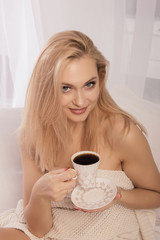 Young woman sitting in bed with a cup of coffie, looking at camera