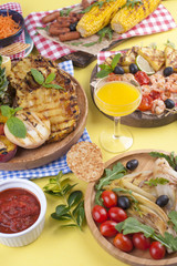 Picnic with grilled food. Sausages and corn on barbecue, shrimp, vegetables and fruits. Delicious summer lunch and plastic dishes. Top view