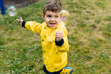 Toddler wearing yellow raincoat playing with bubbles