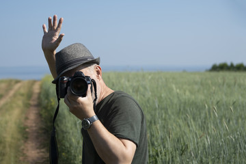 A man with a camera on the background of a wheat field. Concept: summer vacation.