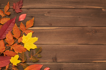 Autumn frame for your idea and text. Autumn fallen dry leaves of yellow, red, orange, lined around the perimeter of the frame on an old wooden board of brown color. The pattern of autumn