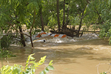 Road Barricade Sawhorse is Swept Away By a Flooded River