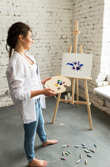 Portrait of beautiful brunette girl wearing in white shirt and jeans, drawing picture with oil paints. Smiling, pretty woman, young female artist dreaming about art and holding brush and palette.