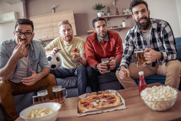 Young men drink beer,eat pizza and cheering for football
