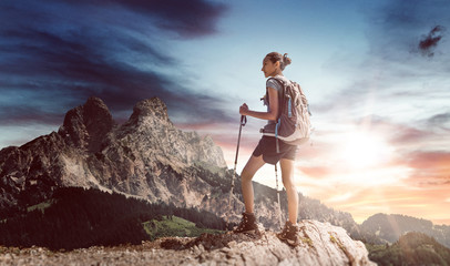 Young female hiker with walking sticks near ledge