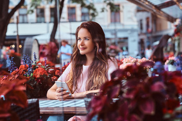 Portrait of a middle age businesswoman with long brown hair holds smartphone while sitting at an outdoor cafe