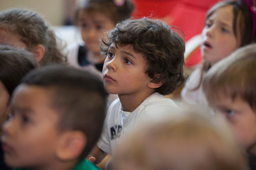 Students listening to their teacher in a kindergarten classroom.