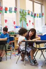 A teacher helping a student in a kindergarten classroom.