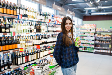 Shopping woman looking at the shelves in the supermarket.  Portrait of a young girl in a market store with shopping cart at alcohol sector.