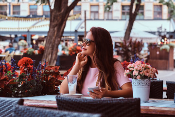 Portrait of a middle age businesswoman with long brown hair in sunglasses holds a smartphone while sitting at a outdoor cafe.