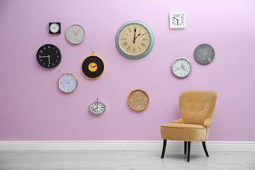 Room interior with many different clocks on wall. Time of day