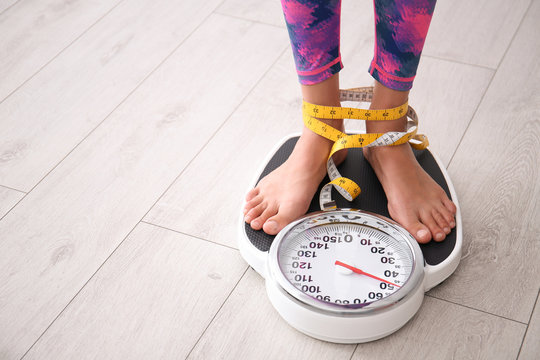Woman tied with tape measuring her weight using scales on floor