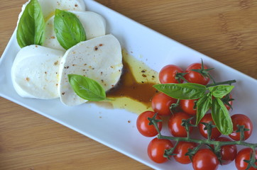 Italian Caprese salad. Close up of mozzarella cheese and cherry tomato salad with balsamic vinegar, olive oil and basil top view