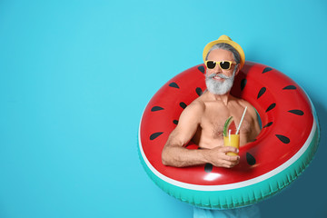 Shirtless man with inflatable ring and glass of cocktail on color background Wall mural