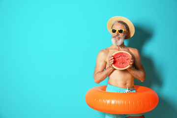 Shirtless man with inflatable ring and watermelon on color background
