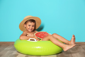Cute little boy with inflatable ring and watermelon near color wall