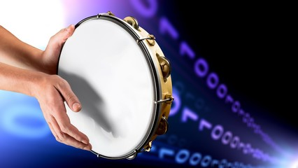 Female hands Playing the tambourine on background