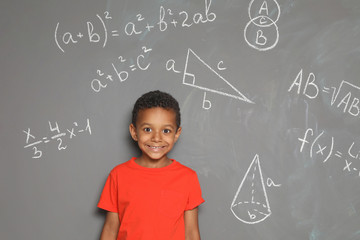 Little African-American school child and mathematical formulas on grey background