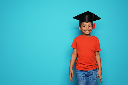 Little African-American school child with graduate cap on color background