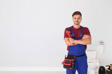 Young man with plumber wrench and toilet bowl on background