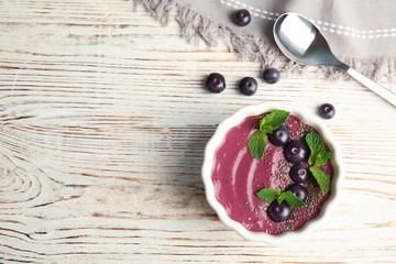 Flat lay composition with bowl of tasty acai smoothie on wooden table
