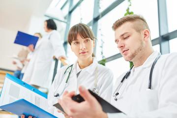 Junge Ärzte in der Ausbildung mit Patientenakte