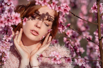 Beautiful young girl with red hair in a gentle peach garden, which blossomed.