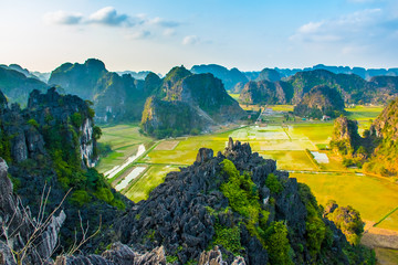 Beautiful sunset landscape viewpoint with green rice fields from the top of Mua Cave mountain, Ninh Binh, Tam Coc in Vietnam