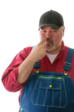 Middle-aged man in dungarees picking his nose