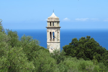 The church tower of Pino surrounded by lush green trees against a blue sea and sky background, Haute-Corse, Corsica, France
