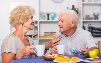 Happy senior couple enjoying conversation over cup of coffee