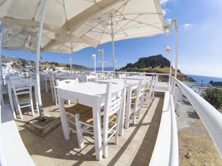 restaurant with white tables and chairs overlooking the sea in greece