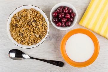 Muesli in bowl, cherry, napkin, spoon, bowl with yogurt